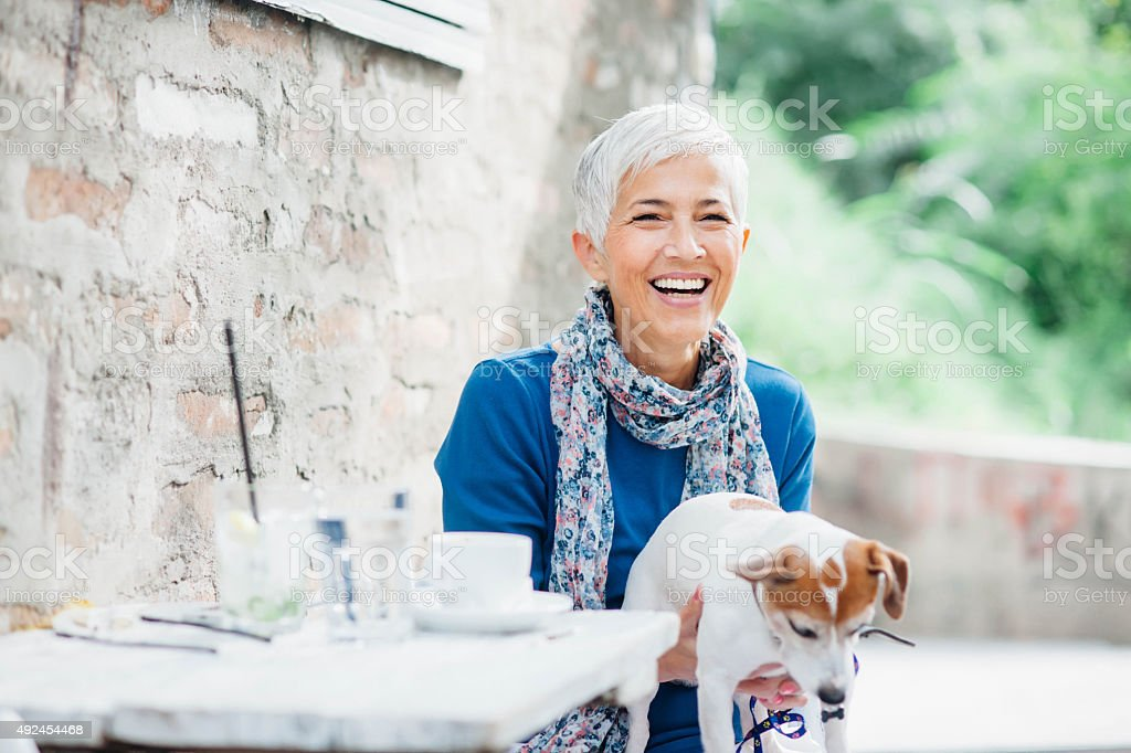 Woman with dog at the cafe stock photo
