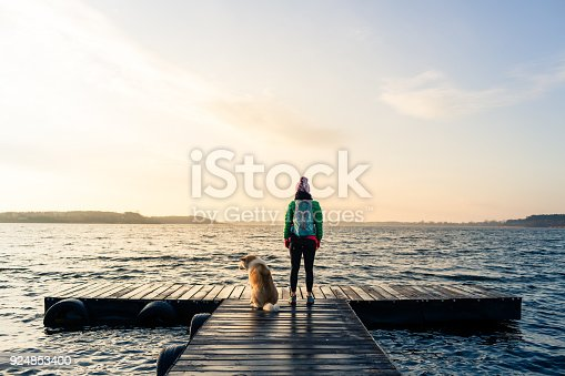 Woman with dog enjoy sunrise and lake, relaxing on bridge. Hiker or tourist looking at beautiful morning view with dog friend, inspirational landscape on beach. Peaceful people and serene concept.