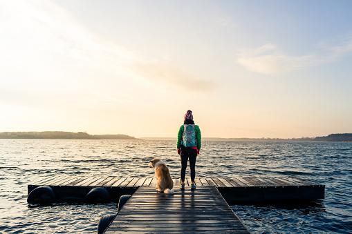 Woman with dog enjoy sunrise at lake, backpacker