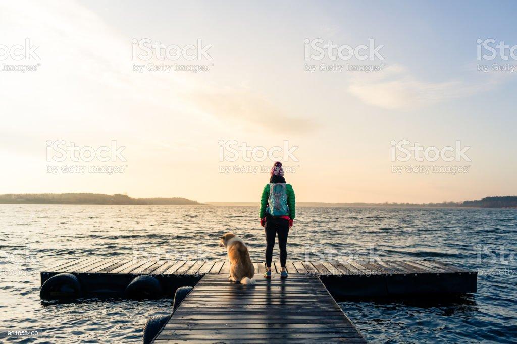 Frau mit Hund genießen Sie Sonnenaufgang am See, Backpacker – Foto
