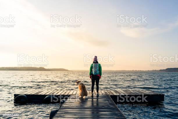 Photo of Woman with dog enjoy sunrise at lake, backpacker