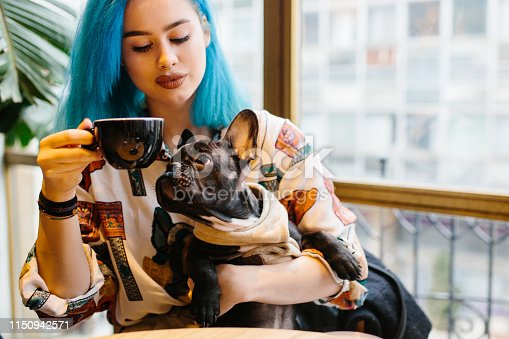 Young hipster woman in cafe with dog drinking coffee