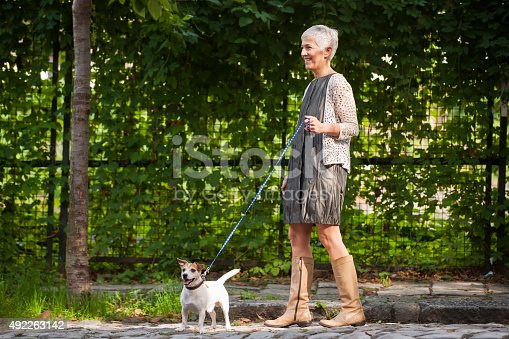 Beautiful mature woman walking with dog, leaves behind them