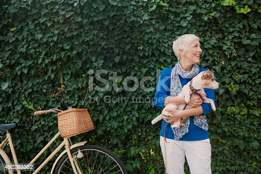 Beautiful mature woman holding dog, leaves behind them and bicycle