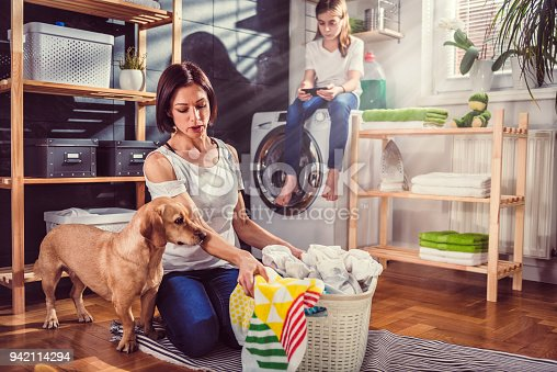 istock Woman with dog sorting clothes on the floor 942114294