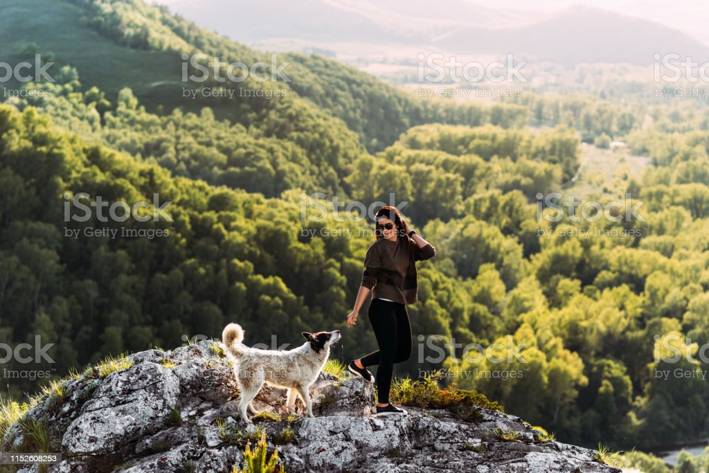 Woman with dog walking in the mountains. Canine friend. Walking with...