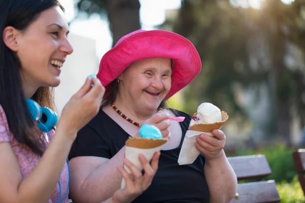 Frau mit Down-Syndrom und ihre Freundin Eis essen und Spaß haben – Foto