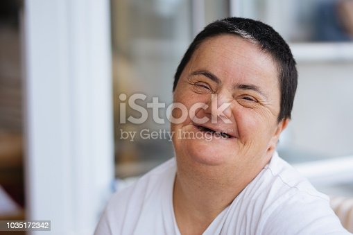 594475880istockphoto Woman with down syndrome smiling 1035172342