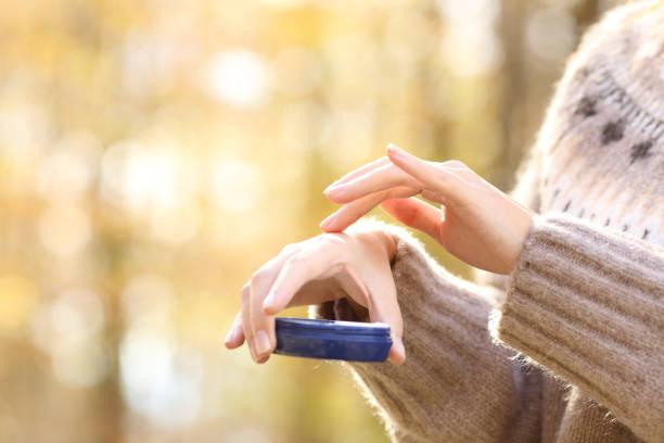 Woman with dry skin applying moisturizer cream in autumn stock photo
