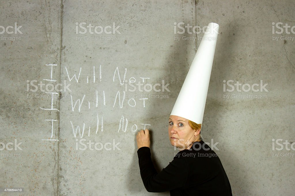 Woman with Dunce Cap Writing I WILL NOT stock photo
