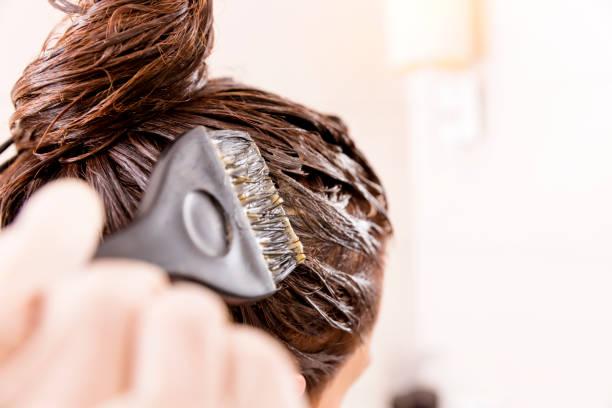 Frau mit dem sterben ihr Haar vor Spiegel in ihrem eigenen Badezimmer. – Foto