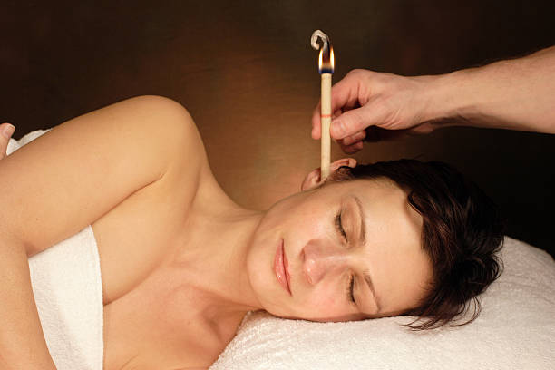 woman with ear candle therapy - hopi stock photos and pictures