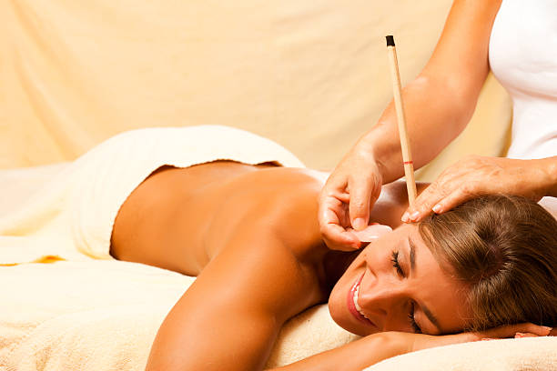 woman with ear candles and gem massage - hopi stock photos and pictures