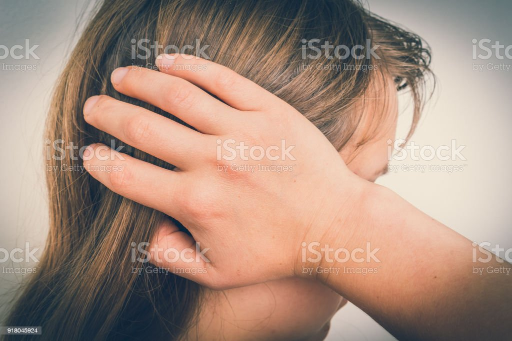 Woman with earache is holding her aching ear - body pain concept