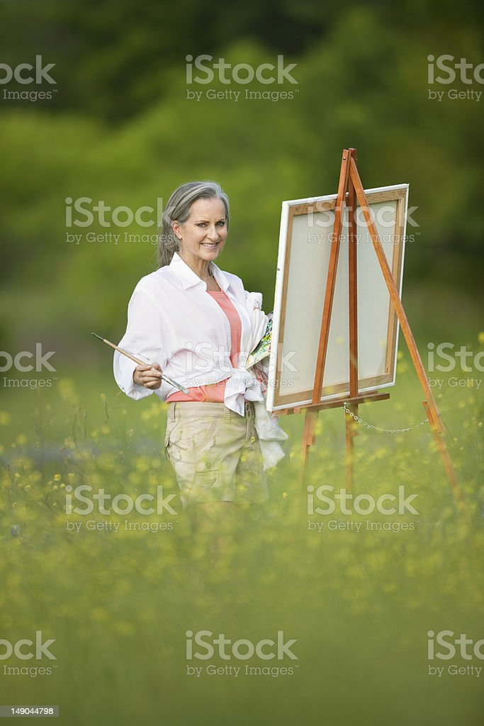 Woman With Easel In Field Of Wildflowers royalty-free stock photo