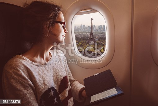 istock Woman with e-book in the airplane travelling to Paris 531423376