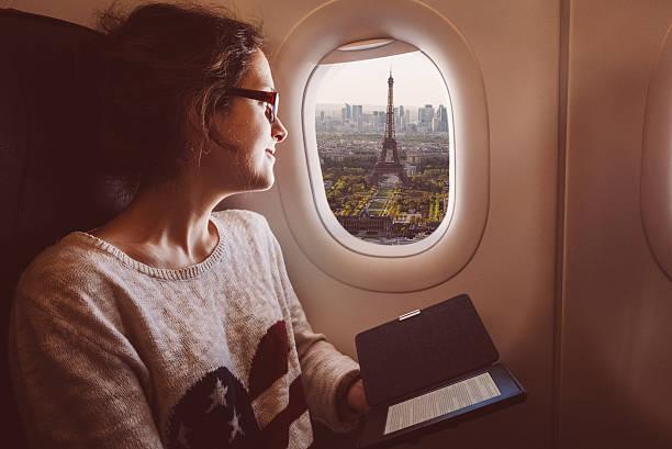 frau mit e-book im flugzeug reisen nach paris - genießen französisch stock-fotos und bilder