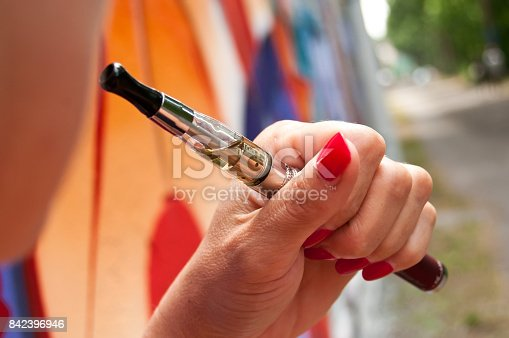 830035654istockphoto woman with e-cigarette in outdoor 842396946