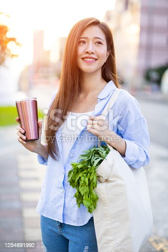 asian woman use reusable eco-friendly ecological cup to drink while commuting in the city