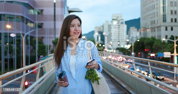 asian woman use reusable eco-friendly ecological cup to drink and use smart phone in the city