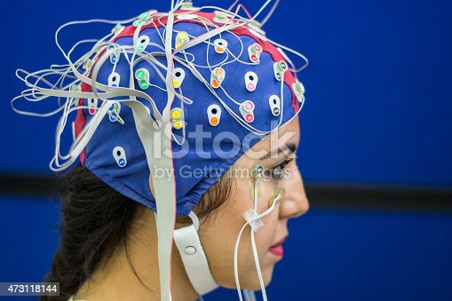 Picture of a young woman with electrodes in her head to record psychophysiological signals for research purposes. Electrocardiogram (ECG), electroencephalogram (EEG) and electrooculogram (EOG) being recorded in a laboratory environment.