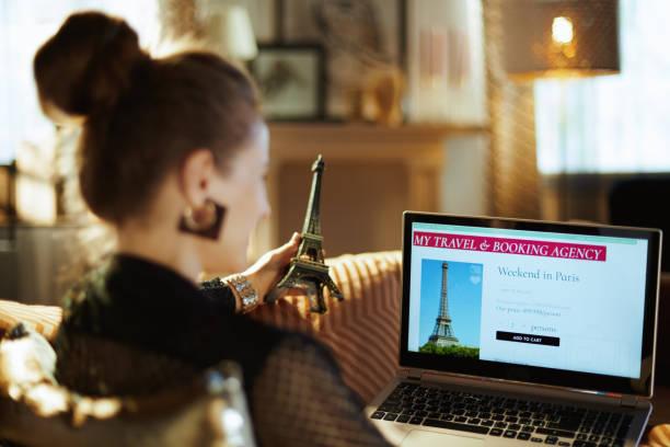 frau mit eiffelturm suche hotel auf online-buchungswebsite - billigflüge buchen stock-fotos und bilder