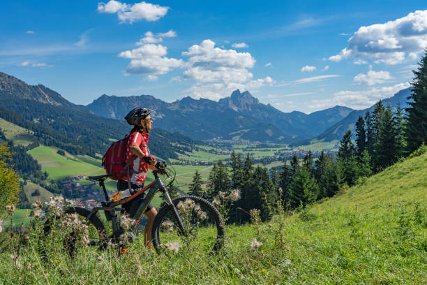 woman with electric mountain bike nice and active senior woman, riding her e-mountainbike in the Tannheim valley, Tirol, Austria with the village of Tannheim and famous summits Gimpel and Rote Flueh mountain biking stock pictures, royalty-free photos & images