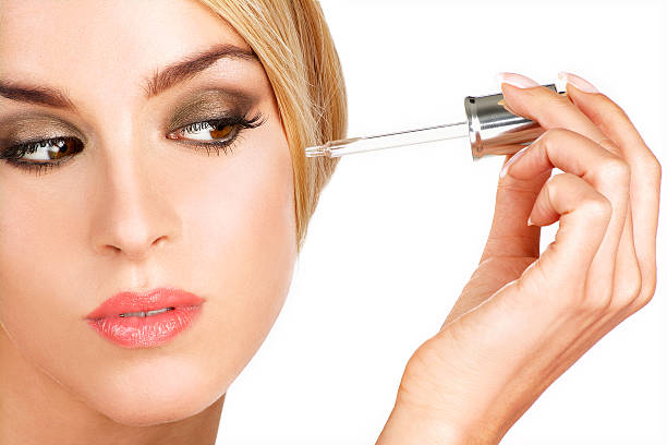 woman with elegant makeup applying serum treatment - serum stock photos and pictures