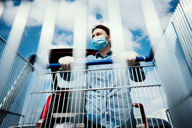 Woman with empty shopping cart wearing protective surgical masks and gloves stock photo