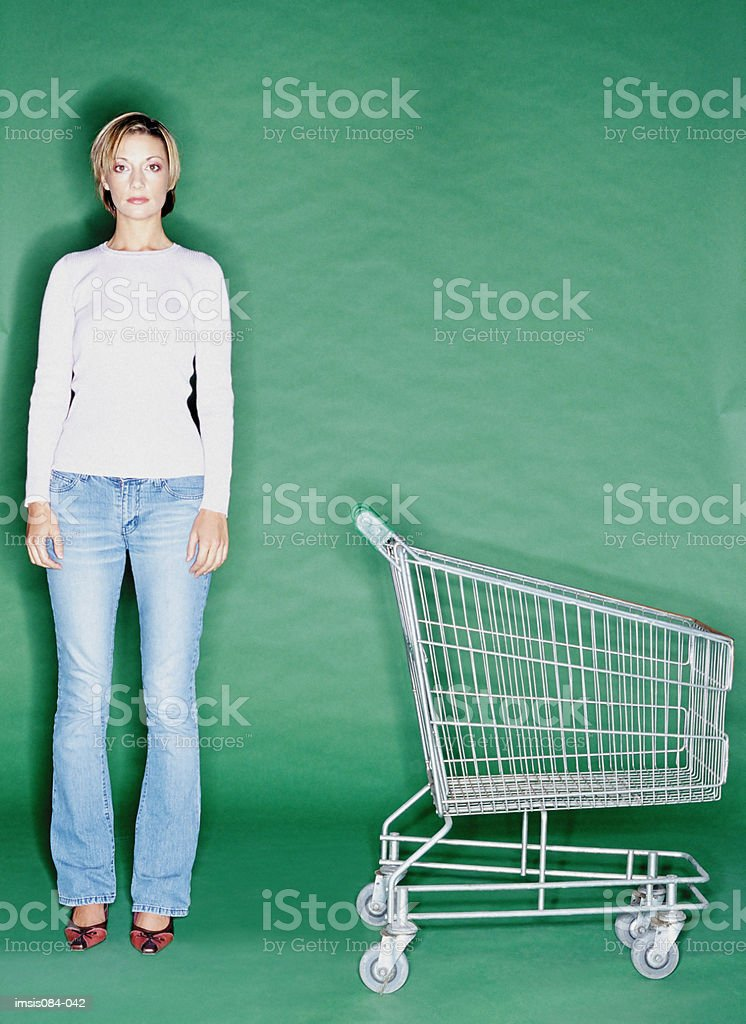 Woman with empty shopping trolley royalty free stockfoto