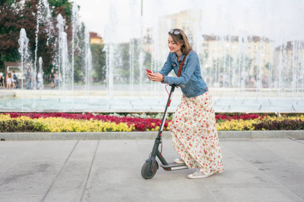 Woman with e-scooter in the city stock photo
