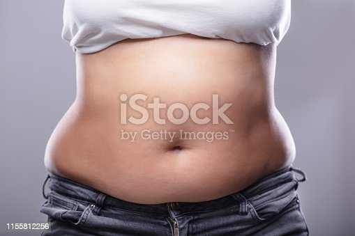 Mid Section Of A Woman With Excessive Belly Fat Against Grey Background