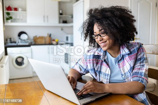 Smiling woman with eyeglasses using laptop at home.