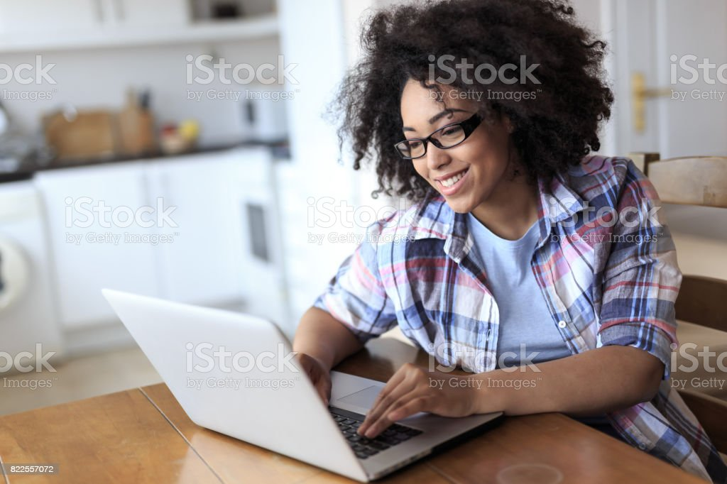 Woman with eyeglasses using laptop at home stock photo