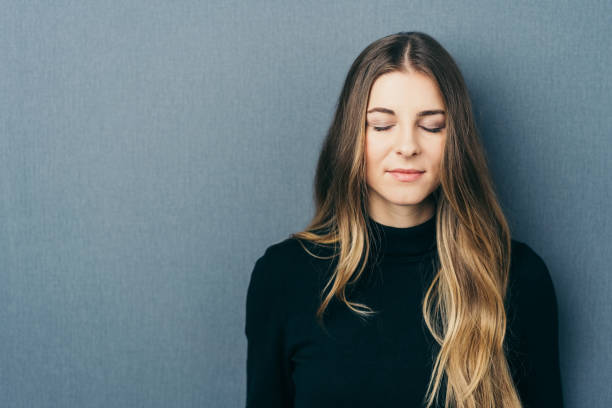 Woman with eyes closed by wall with copy space Young long-haired woman with eyes closed standing against wall with copy space eyes closed woman stock pictures, royalty-free photos & images