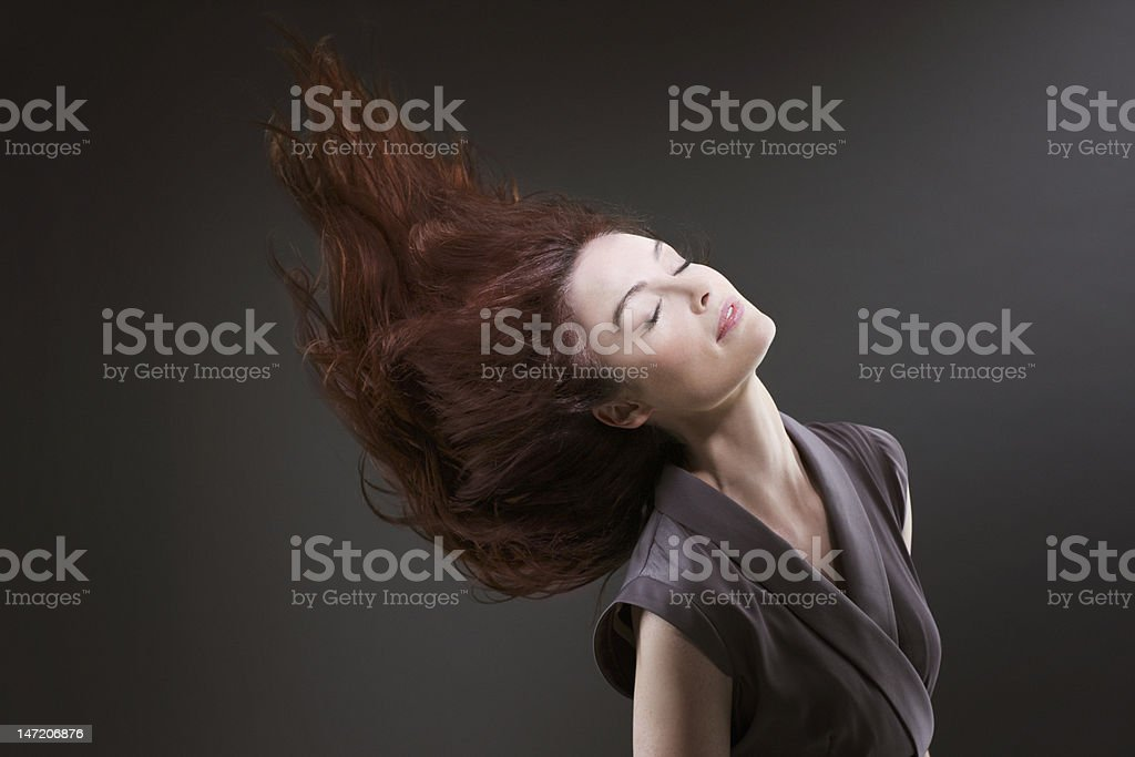 Woman with eyes closed flipping hair stock photo