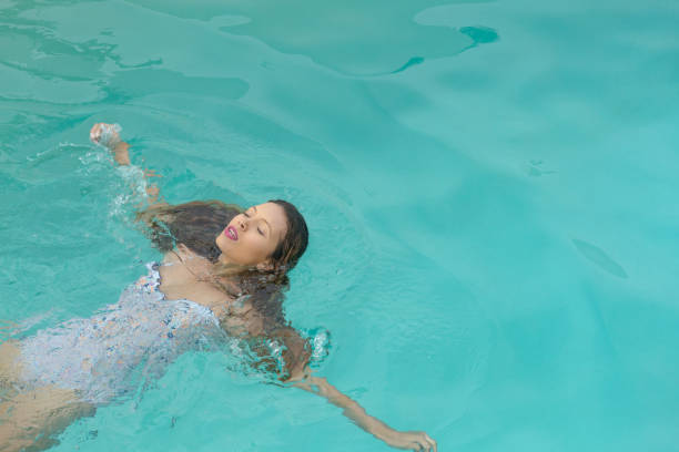 Woman with eyes closed floating in swimming pool at the backyard of home stock photo