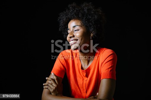 Young woman with eyes closed over black background. Female is smiling while crossing arms. She is wearing orange top.