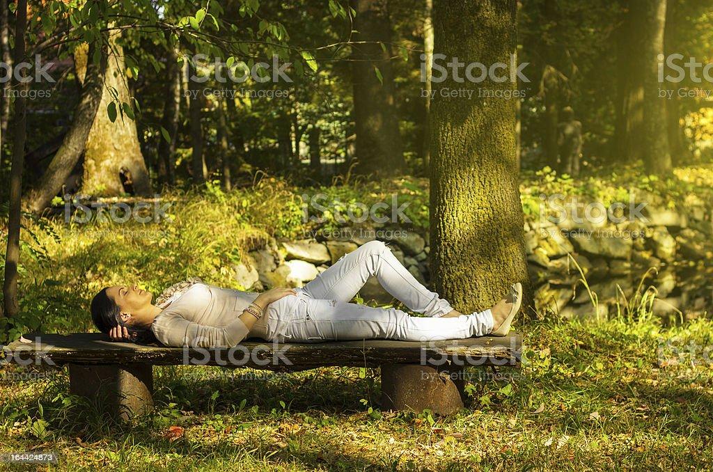 Frau mit Augen geschlossen entspannenden auf einer Bank in der Natur – Foto