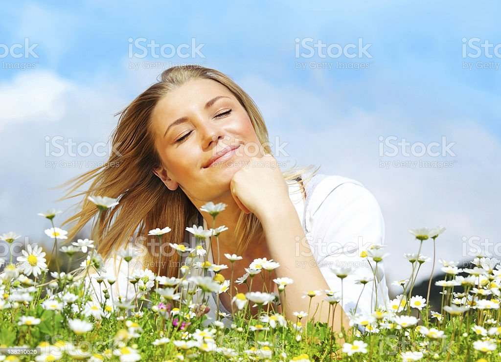 Woman with eyes closed resting hand on chin on daisies royalty-free stock photo