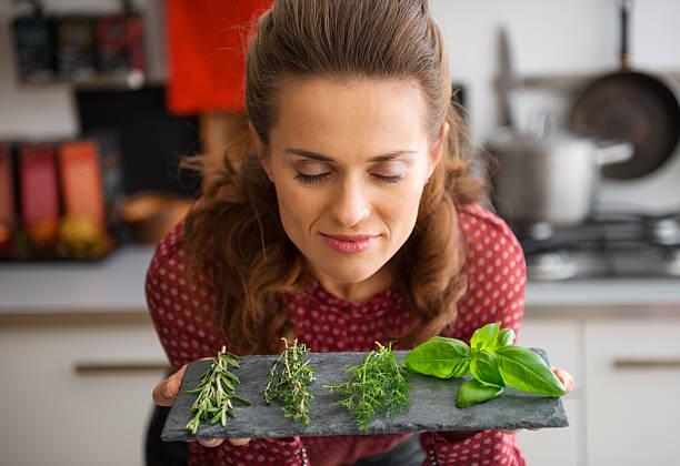 woman with eyes closed smelling fresh herbs - food woman to smell bildbanksfoton och bilder