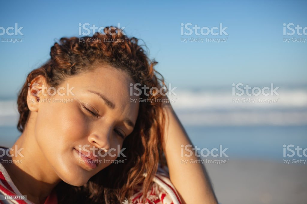 Portrait of beautiful mixed race woman with eyes closed wrapped in...