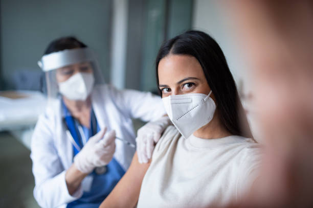 Woman with face mask getting vaccinated and taking selfie in hospital, coronavirus and vaccination concept. stock photo
