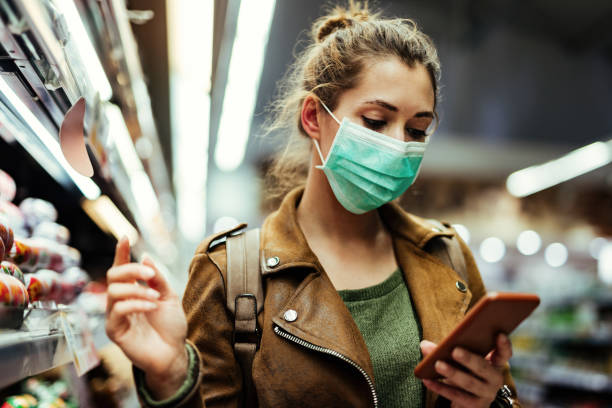 Woman with face mask going through check list on smart phone while buying in supermarket. stock photo