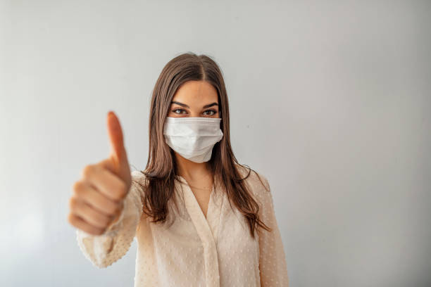 Woman with face mask protection of Coronavirus showing thumb up Portrait of young woman wearing face protective mask to prevent Coronavirus and anti-smog. Portrait of young woman wearing face mask. Thumb up. pollution mask stock pictures, royalty-free photos & images