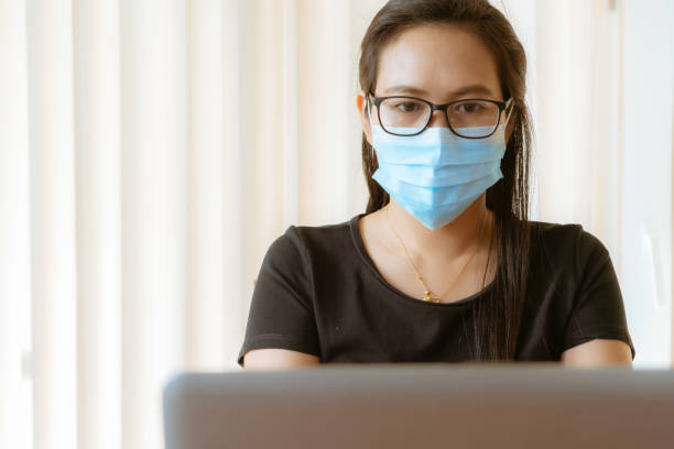 woman with face mask protection while working, Coronavirus, air pollution, allergy sick woman with medical mask stock photo
