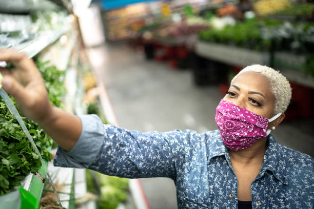 Woman with face mask shopping at supermarket stock photo