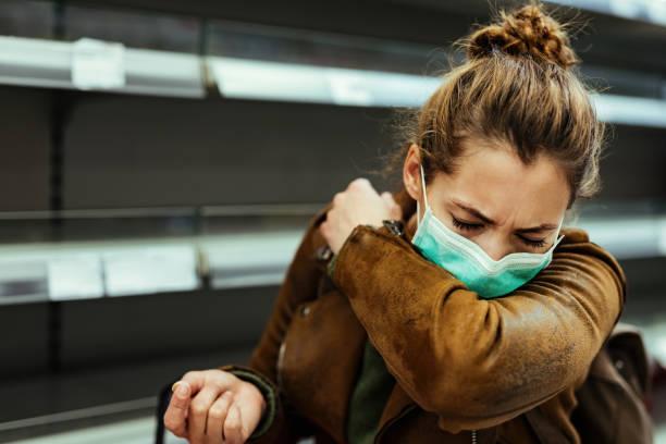 frau mit gesichtsmaske niest in den ellenbogen beim einkaufen in lebensmittelgeschäft. - erkältung und grippe stock-fotos und bilder