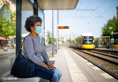 Woman wearing medical face mask commuting in a tramway train during corona virus outbreak. Female travelling in metro during Covid-19 pandemic.