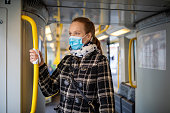 Woman wearing medical face mask commuting in a subway train during corona virus outbreak. Female travelling in metro during Covid-19 pandemic.